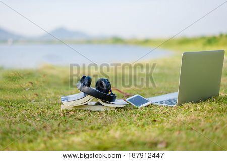 Enjoy listening music on the grass field of the park in the morning