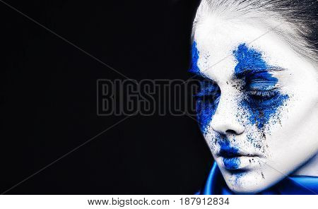fashion model girl portrait with colorful powder make up. Beauty woman with bright blue makeup and white skin. Abstract fantasy make-up, art design.