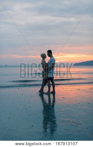 Couple Embracing On Beach At Sunset, Young Tourist Man And Woman Hug On Seaside While Summer Vacation