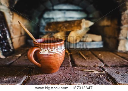 A Clay Pot With Traditional Oven On The Background