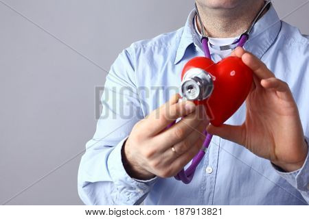 Healthcare and medicine concept - close up of male doctor hands holding red heart and medical stethoscope.