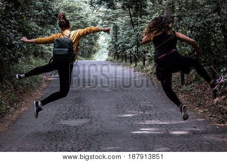 Heel click on forest path by young adult girls / women sisters with hair in bun and leather backpack with mustard yellow sweater jumping in the air