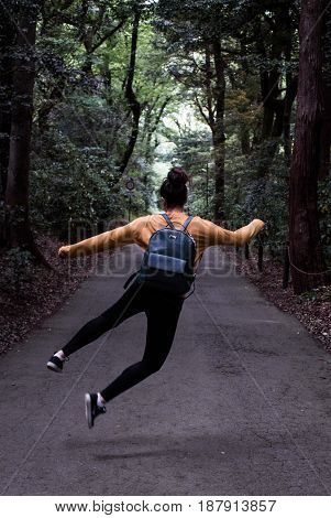 Heel click on forest path by young adult girl woman with hair in bun and leather backpack with mustard yellow sweater jumping in the air