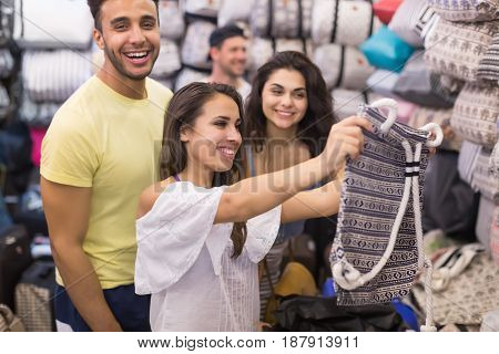 Young People Group On Shopping Choosing Bag, Man And Woman Happy Smiling Buyers In Retail Store Selecting Female Purse