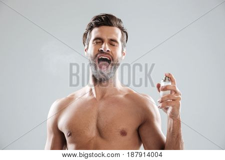 Bearded man with opened mouth using toilet water isolated