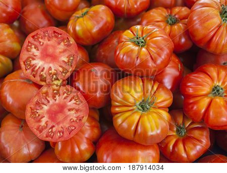Two halves of juicy ripe tomato in the section. Fresh tomatoes. Red tomatoes. Village market organic tomatoes. Qualitative background from tomatoes