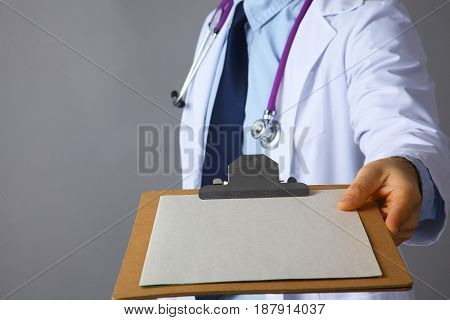 The doctor in a white coat with a stethoscope holding a folder .