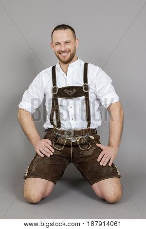 An image of a man in bavarian traditional lederhosen on his knees