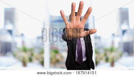 Digital composite of Businessman showing stop gesture in city