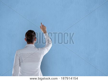 Digital composite of Rear view of businesswoman pointing on blue background
