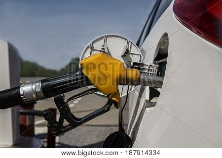 Refueling at the gas station. Old yellow pistol with a hose in the gas tank of the car. Close up.
