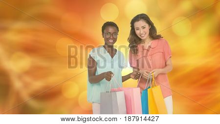 Digital composite of Smiling women with shopping bags over blur background