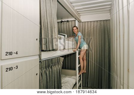 Girl standing in a stylish hostel bedroom. Young woman climbing the bed stairs bed in hotel room with two-levels beds. Evening grey curtain and wall