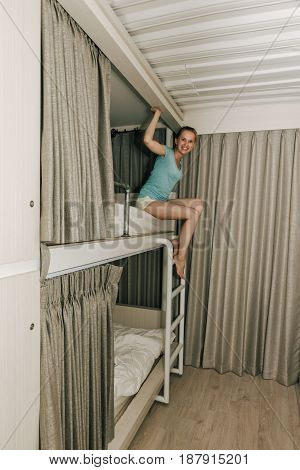 Girl sitting in a stylish hostel bedroom. Young woman climbing the bed stairs bed in hotel room with two-levels beds. Evening grey curtain and wall