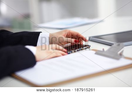Young woman sitting at the desk with folder and phone.