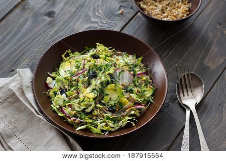 Salad from brussels sprouts with radish, raisins and sprouts of wheat. Healthy diet detox food. On a wooden background in a rustic style