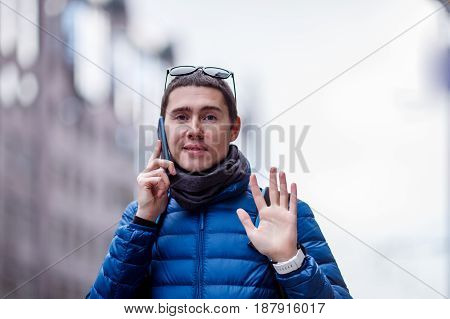 Man talking on phone and waving his hand in the city