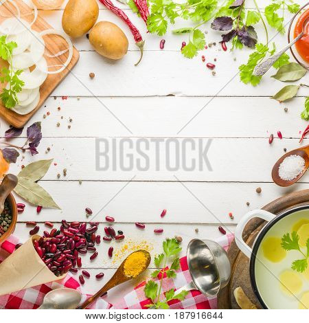 Preparation of soup at home. Rustic white background with vegetables and ingredients around the perimeter. View from above. Lots of copy space.