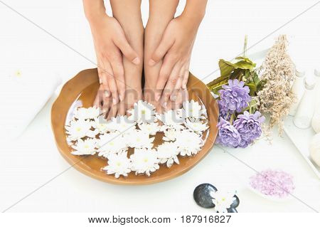 Spa treatment and product for hand and foot spa with flowers and water wooden background; select and soft focus