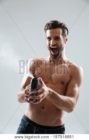 Joyful bearded man playing with deodorant and screaming isolated