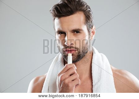 Man with towel looking camera and using lipstick isolated