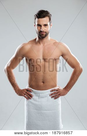 Serious young muscular man wearing towel looking camera isolated
