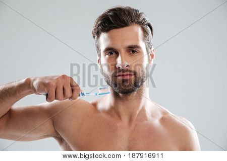 Serious bearded man holding toothbrush isolated