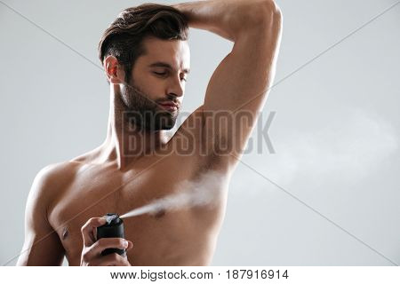 Horizontal image of young man using deodorant isolated