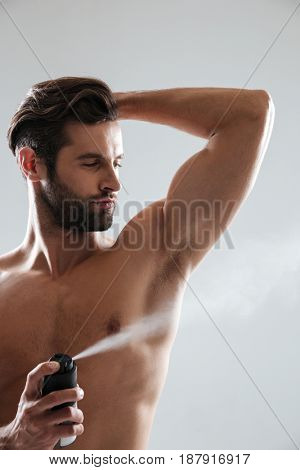 Vertical image of muscular young bearded man with deodorant isolated