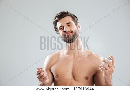 Young man closing eyes while using perfume isolated over grey