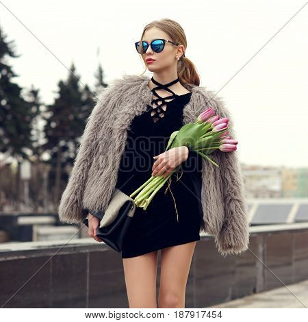 Stylish red hair girl with ponytail wearing short black dress, fur coat and sunglasses. Young woman with pink tulips