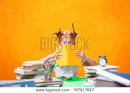 The Redhead teen girl with lot of books sitting with notebook at table on orange studio background. The education and back to school concept