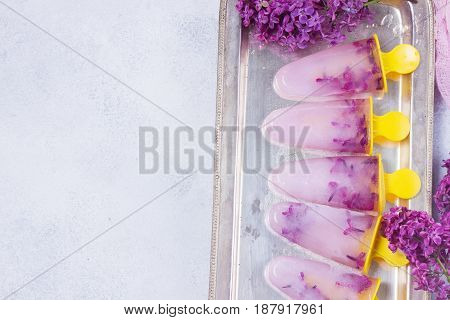 Popsicles with lilac flowers on gray stone background border
