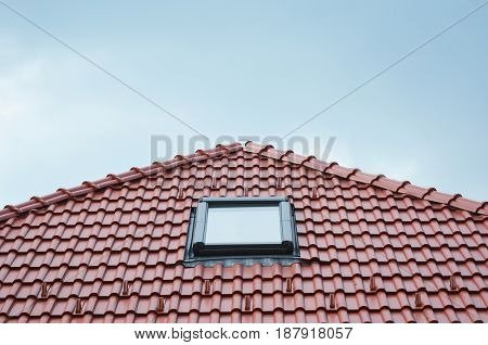 Modern Roof Skylight Window on Red House Clay Ceramic Tiles Roof. Roofing Construction.