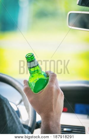 Man driving a car with a bottle of beer or other alcohol drink. Don't drink and drive concept