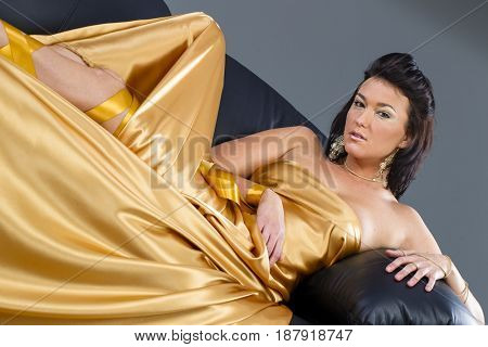 A brunette model in a studio environment with gold highlights.