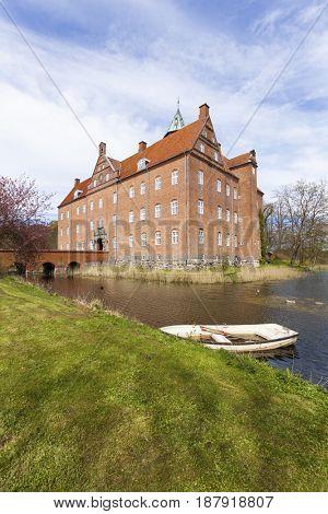 17th century water castle Sostrup, Gjerrild, Denmark. Boat on moat in foreground.