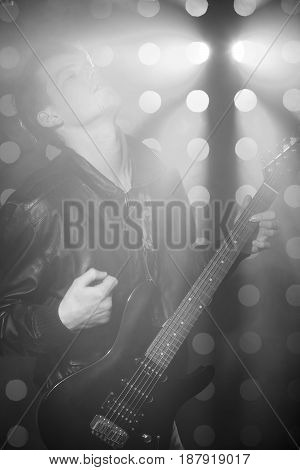Black and white photo of young attractive rock musician playing electric guitar and singing.