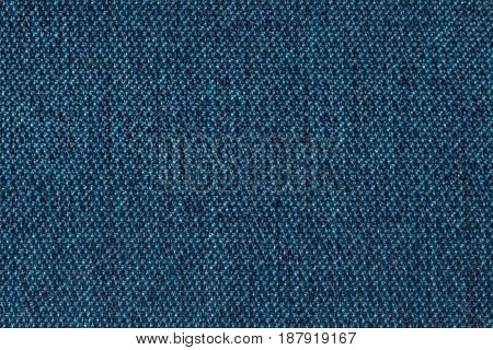Navy blue background from woolen texture textile closeup. Structure of the denim wicker fabric macro.