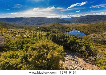 High angle view of Wombat Pool surrounded by green mountains at Cradle mountain, Lake St Clair National Park. Autumn in Tasmania, Australia