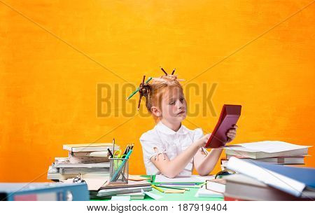 The Redhead teen girl with lot of books sitting with calculator at table on orange studio background. The education and back to school concept