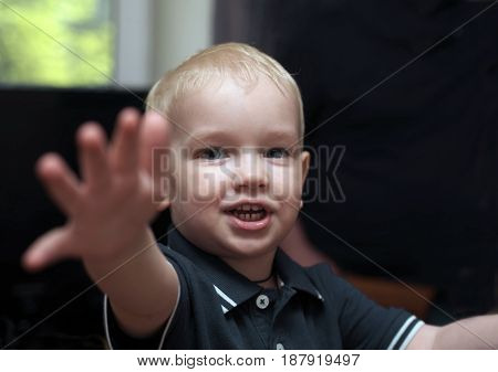 A little boy with blonde hair reaching hand asking for help or attention selective focus photo