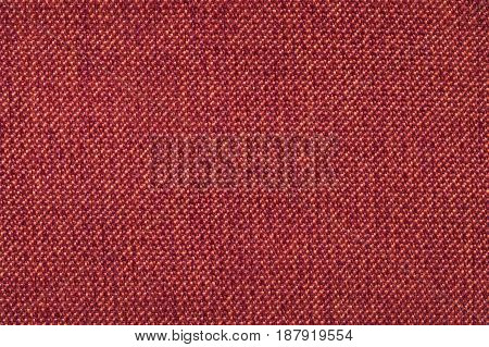 Red background from woolen texture textile closeup. Structure of the orange wicker fabric macro.