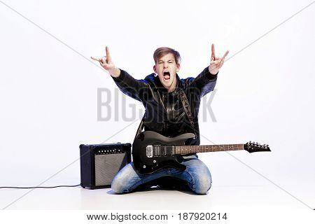 young expressive handsome rock musician playing electric guitar and singing. Rock star making rock gesture
