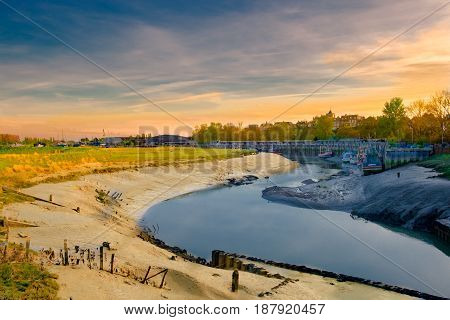 River Rother at sunset at low tide with its fishing boats and Rye town in the background, East Sussex, England, UK