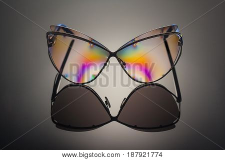 Front view of stylish transparent polarized colorful reflected sunglasses in metal frame with unfocused background and removed logos