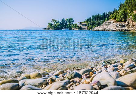 Pebble beach near Kalami with pine and cypress trees and an yacht at anchor in a bay on background. Corfu Island, Greece.