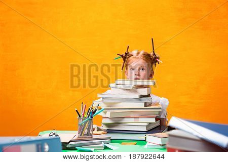 The Redhead girl with lot of books sitting at table on orange studio background. The education and back to school concept
