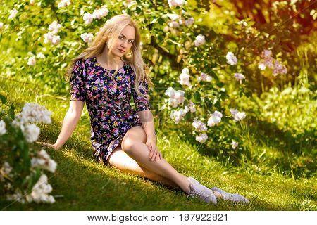 Beautiful blonde woman portrait in lilac tree flowers - close up beauty portrait