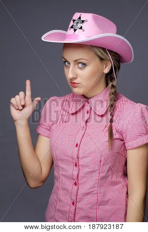 Beautiful glamour cowboy showing gun by fingers on gray